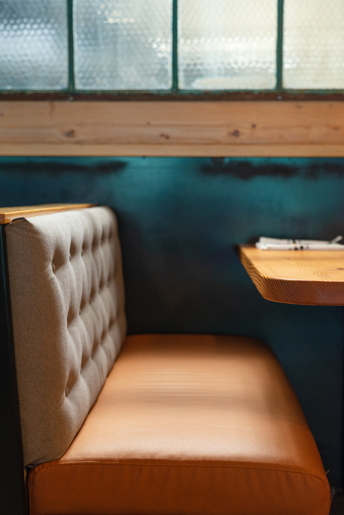 Warm Leather Booth In Front of Reclaimed Timbers and windows